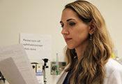 Dr. Laura Lewandowski reviews printouts in a medical exam room