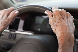 older woman's hands on steering wheel