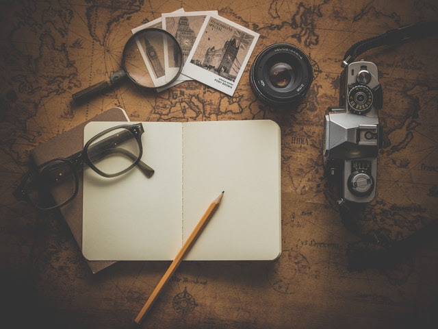 travel map and photos with glasses and open journal