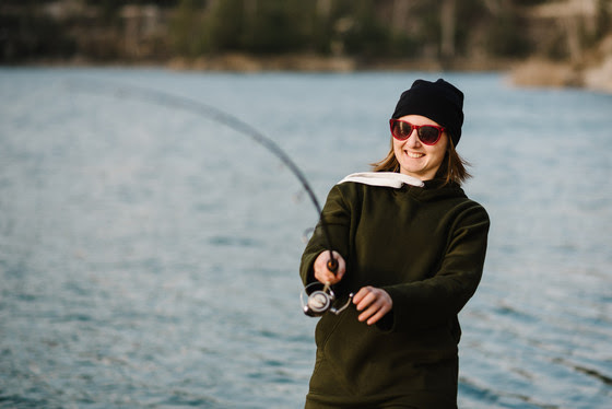 Woman fishing with rod, spinning reel
