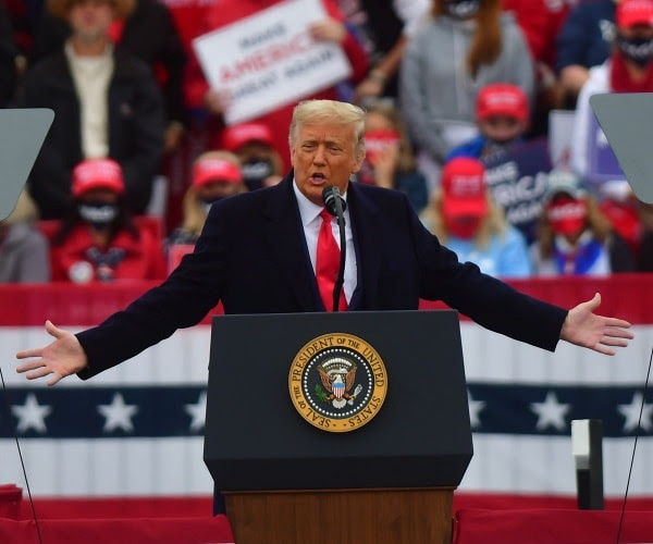 Trump stands in a power pose at a rally