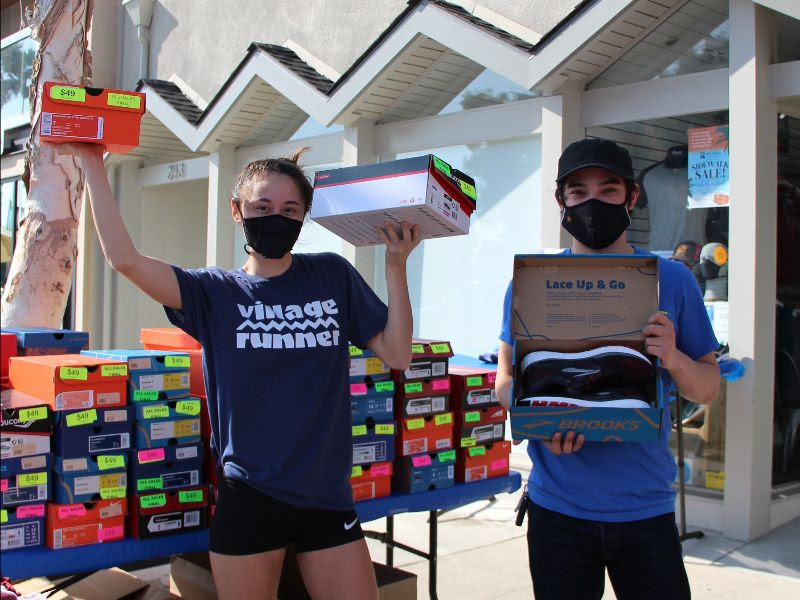 Village Runner crew members holding up sale shoes in front of the Redondo Beach store.