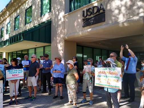 """A photo of the crowd near Garamendi's office on Thursday's Deadline for Democracy rally. People hold signs such as """"Pass the For the People Act Now"""", """"Thank you Garamendi for co-sponsoring For the People Act- S1"""" and """"We need S1 to pass"""""""