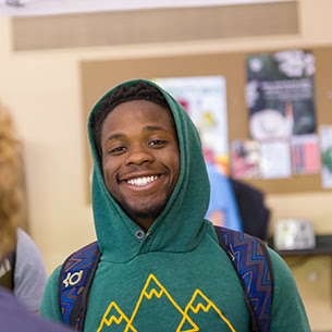 Student wearing a green hoodie standing on campus