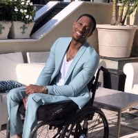 An African American man wearing a blue suit with a white t-shirt. He is smiling sitting on a wheelchair with plant pots behind him.