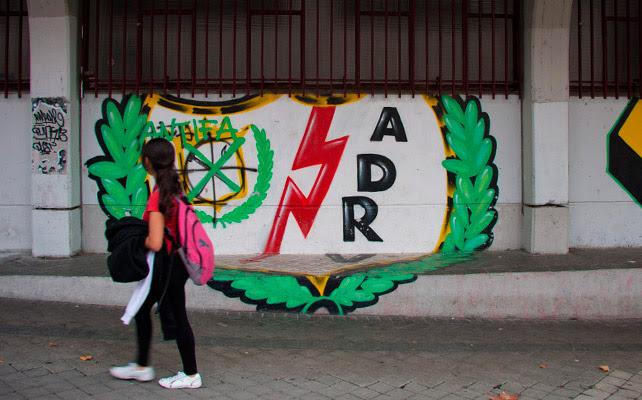 Una niña pasa por delante de un escudo del Rayo pintado en la fachada del estadio de Vallecas.