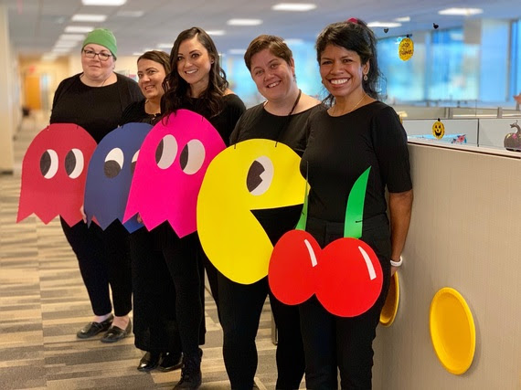 Five WDE staff wear halloween PacMan Halloween costumes. Everyone is dressed in black with posterboard hanging around their neck that shows PacMan, cherries, and three of the ghosts that chase PacMan throughout the game.