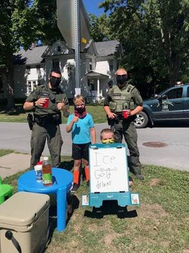 Two kids stand at their lemonade stand for a picture with two ECOs