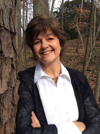 Smiling woman leans against tree