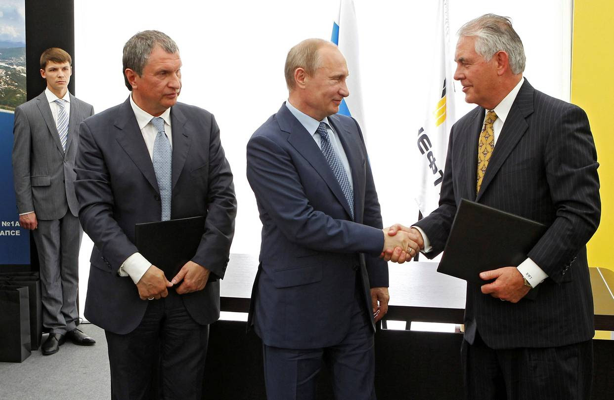 In June 2012, Russia's President Vladimir Putin (center), watched by Rosneft Chief Executive Igor Sechin, shook hands with Rex Tillerson, who was then Exxon Mobil chief executive and is now U.S. secretary of state, at a signing ceremony at a Rosneft refinery in the Black Sea town of Tuapse..