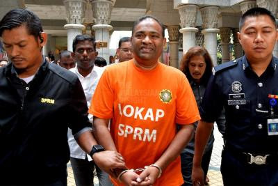 How come convicted Najib remains in his blue suit when his side-kick gets the orange and bracelets?