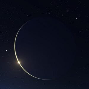 Sliver of light of the crescent new moon in a black sky