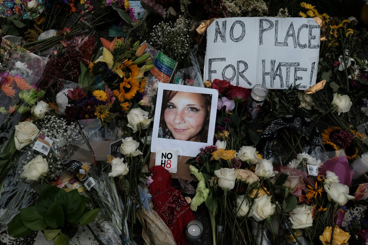 A photograph of Charlottesville victim Heather Heyer is seen among flowers left at the scene of the car attack that killed her. (Justin Ide/Reuters)