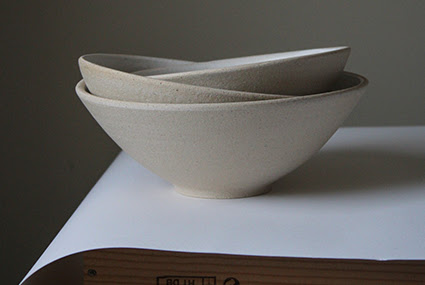A photograph of three stacked beige ceramics bowls by Hazel Frost. They are displayed against a beige wall and on a white piece of paper and wooden table.