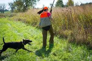 hunter and dog head into tall grass