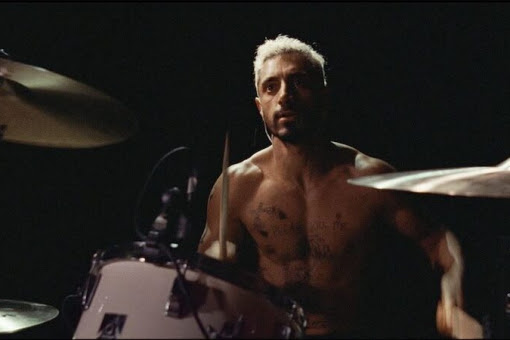 Ruben from the film Sound of Metal with bleach blonde hair sat in front of a drum kit topless