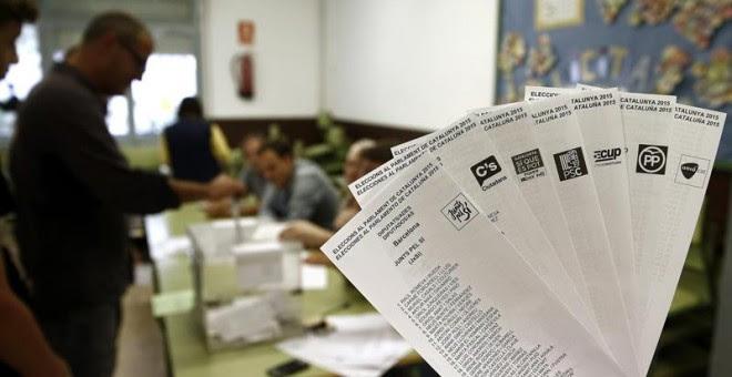 Una persona muestra las papeletas de los diferentes partidos que concurren a las elecciones al Parlamento Catalan que se celebran hoy en Cataluña, mientras una persona deposita su voto en la urna en una jornada en la que un total de 5.314.736 personas est