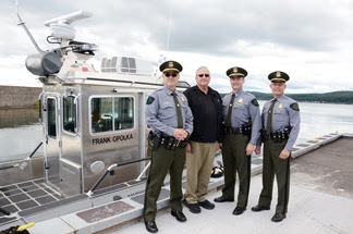 DNR Law Enforcement Division staff with honoree Frank Opolka in front of patrol boat.