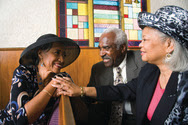 Two older African-American women and one African-American man sitting in a church