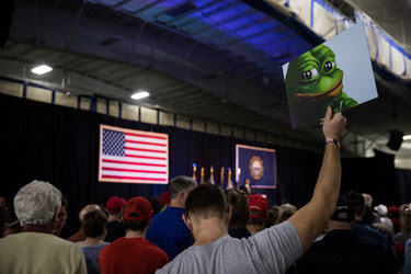 A man held a Pepe the Frog picture during a rally for Donald Trump in Bedford, N.H., on Sept. 29. The Anti-Defamation League includes Pepe the Frog in its database of hate symbols, linked with white supremacy.