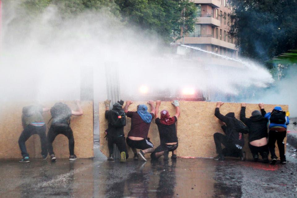 Resistiendo los chorros de los camiones hidrantes en las calles de Santiago.