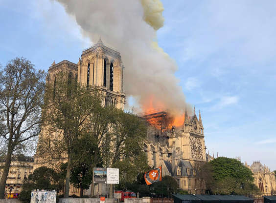 Slide 24 of 31: Notre Dame cathedral is burning in Paris, Monday, April 15, 2019. Massive plumes of yellow brown smoke is filling the air above Notre Dame Cathedral and ash is falling on tourists and others around the island that marks the center of Paris. (AP Photo)