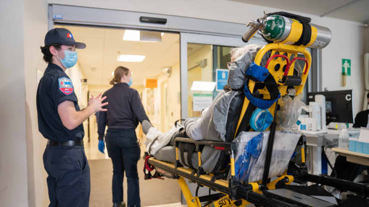 Paramedics escort a pandemic patient into the hospital on a stretcher