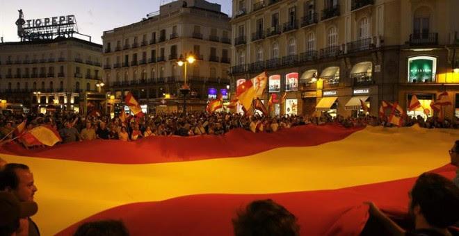 Un grupo de personas desplegó una gran bandera de España en la Puerta del Sol de Madrid en una concentración convocada a través de las Redes Sociales en contra de la independencia de Catalunya./ EFE