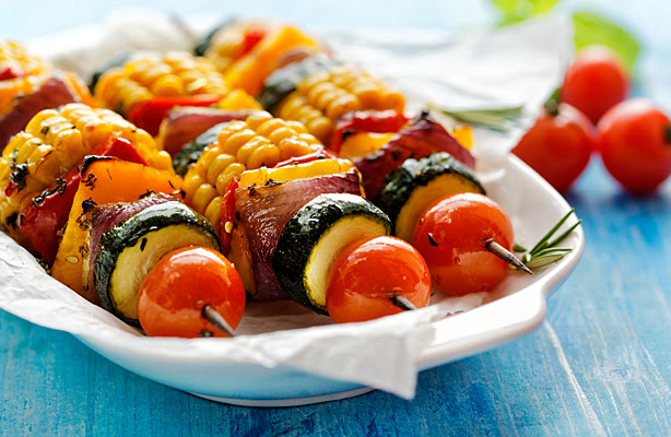 An outdoor buffet dish featuring healthy vegetable kabobs.