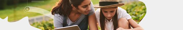 Mulher e criança ao ar livre: Mãe e filha ao ar livre usando notebook.