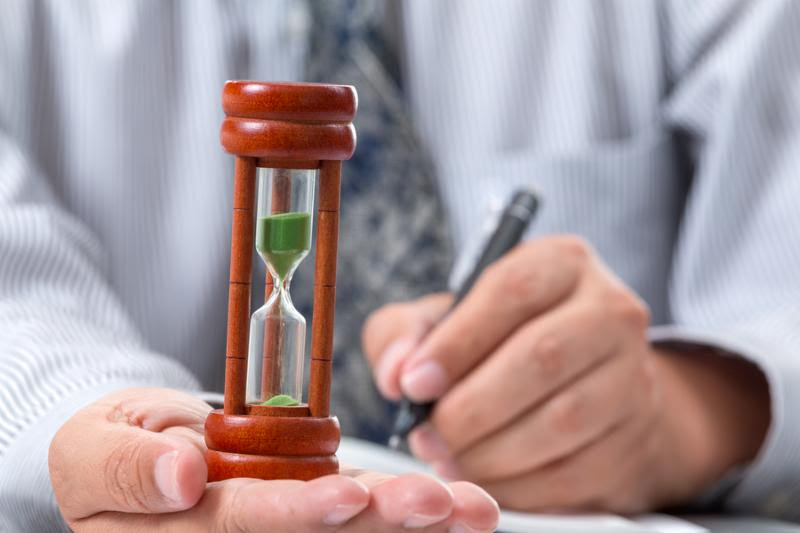 Close up hour glass laying on right hand of businessman taking note
