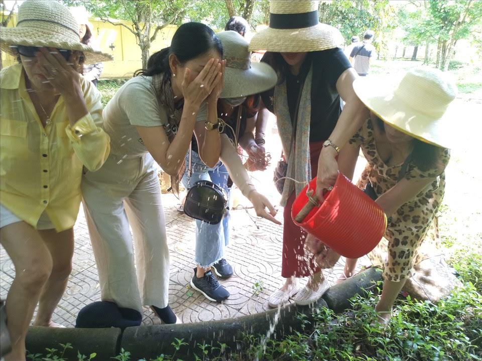Gội rửa bằng nước lấy từ giếng cổ với niềm tin giúp cơ thể được khỏe mạnh. Ảnh: K.Q