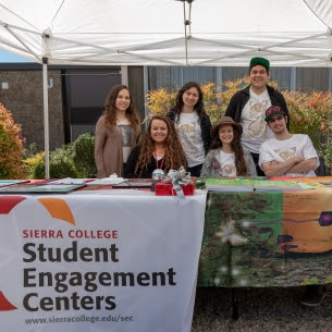 Six students sitting and standing at a Student Engagement Centers table on campus