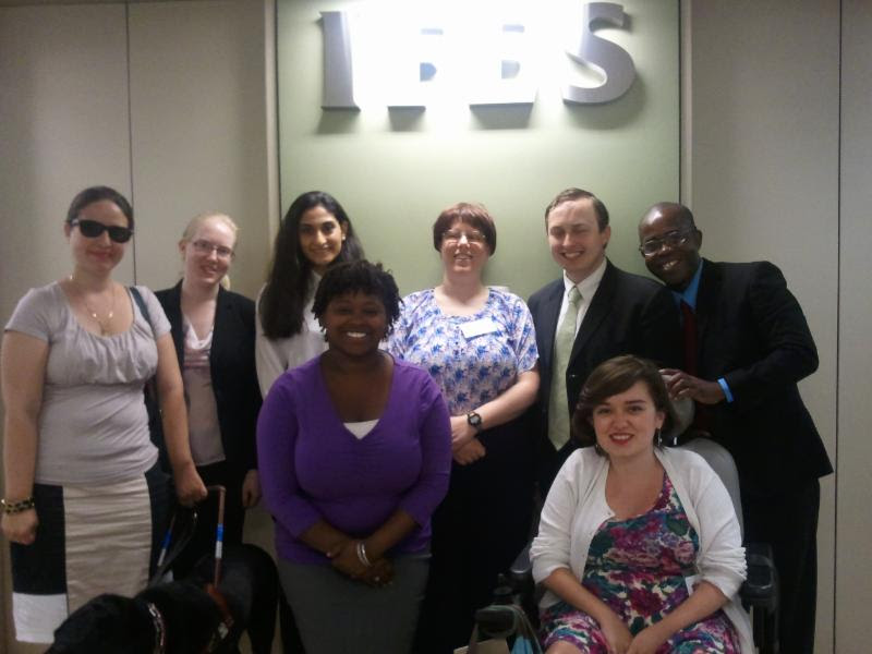 A group of eight people in business suits blouses or dresses smile at the camera One has a guide dog another is seated in the wheelchair On the wall behind them is the logo for the International Federation Electoral Systems IFES