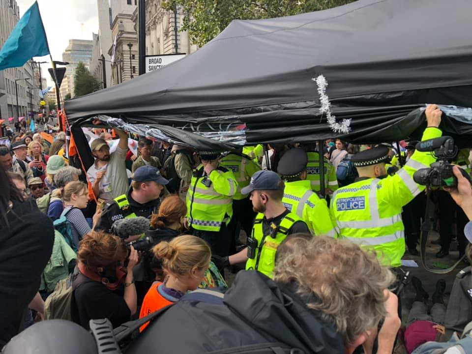 A group of around 10 police officers attempting to seize a black gazebo, with rebels and people with cameras surrounding them.