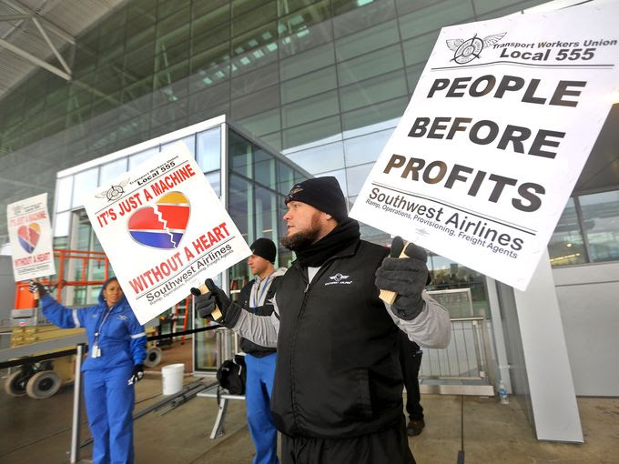 TWU 555 Indianapolis representative Shaun Burris protests with other Southwest Airlines employees at the Indianapolis International Airport, Tuesday, December 16, 2014. Members of the Transit Workers Union (TWU) 555, including those who work outside on the ramp, operations, cargo and provisioning, picketed at the airport saying they haven't had a contract in over 3 1/2 years. (Photo: Kelly Wilkinson/The Star)