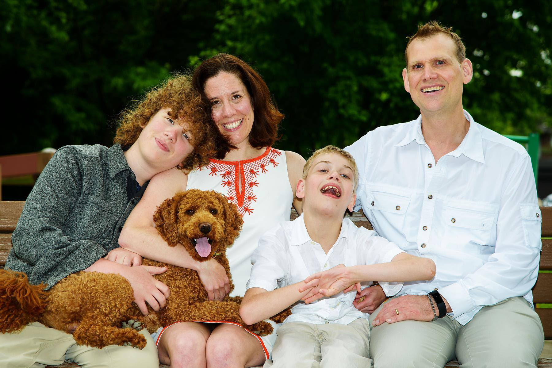 A family sitting on a bench. One son on the left is having curly red hair and a cute labradoodle on his lap. Next to him is his mom, a woman with brown hair who smiles brightly. Next to her, the younger son who wears a white shirt. And on the right side is the dad wearing a white shirt as well.