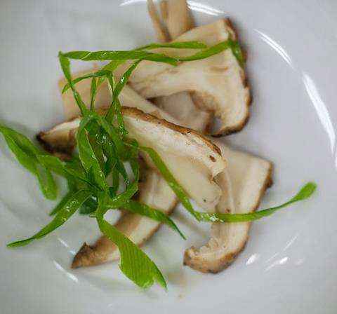 sliced mushrooms with garnish on a white plate