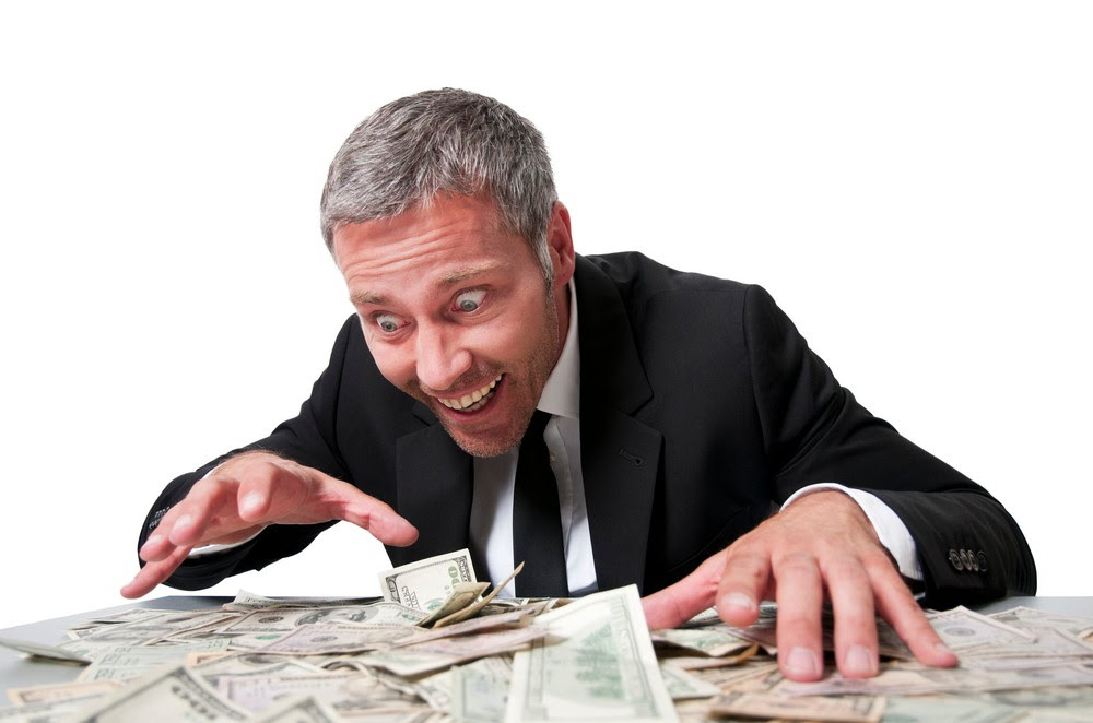 Man looking over a pile of money excitedly