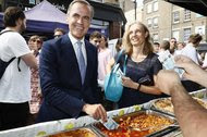 Mark Carney, governor of the Bank of England, tests a new polymer 5-pound note by dipping it in a tray of food as he buys lunch at Whitecross Street Market in London.