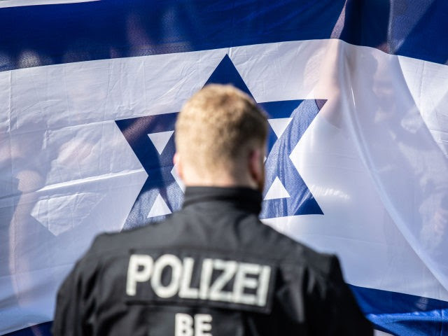 BERLIN, GERMANY - JUNE 01: A German policeman stands in front of counter demonstrators waving an Israeli flag as the annual Al-Quds march pass by (not pictured) on June 1, 2019 in Berlin, Germany. Critics accuse the Al-Quds marchers of anti-Semitism Quds Day was originally held in Iran and spread …