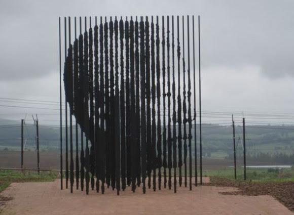 Escultura en honor a Nelson Mandela. Consiste en 50 placas de acero con 10 metros de altura cada una, cortadas con láser e insertadas en el paisaje, representando el 50º aniversario de la captura y puesta en prisión de Nelson Mandela, el 6 de agosto de 1962. La escultura está en el terreno donde quedaba la prisión, sobre el área donde estuvo su celda por 27 largos años. En un punto específico de observasión, la perspectiva de las columnas sorprende al verse la imagen de Nelson Mandela. El escultor fue Marco Cianfanelli quien nació en Johannesburgo en 1970 y se graduó con la distinción en Bellas Artes, en la Universidad de Witwatersrand en 1992. Foto: Dra. Sonia Morell Quintana