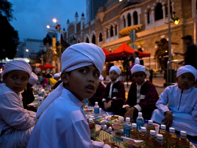 Children break their fast on the first day of Ramadan in Kuala Lumpur, Malaysia.