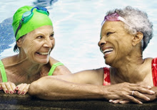 Two smiling women in a swimming pool.