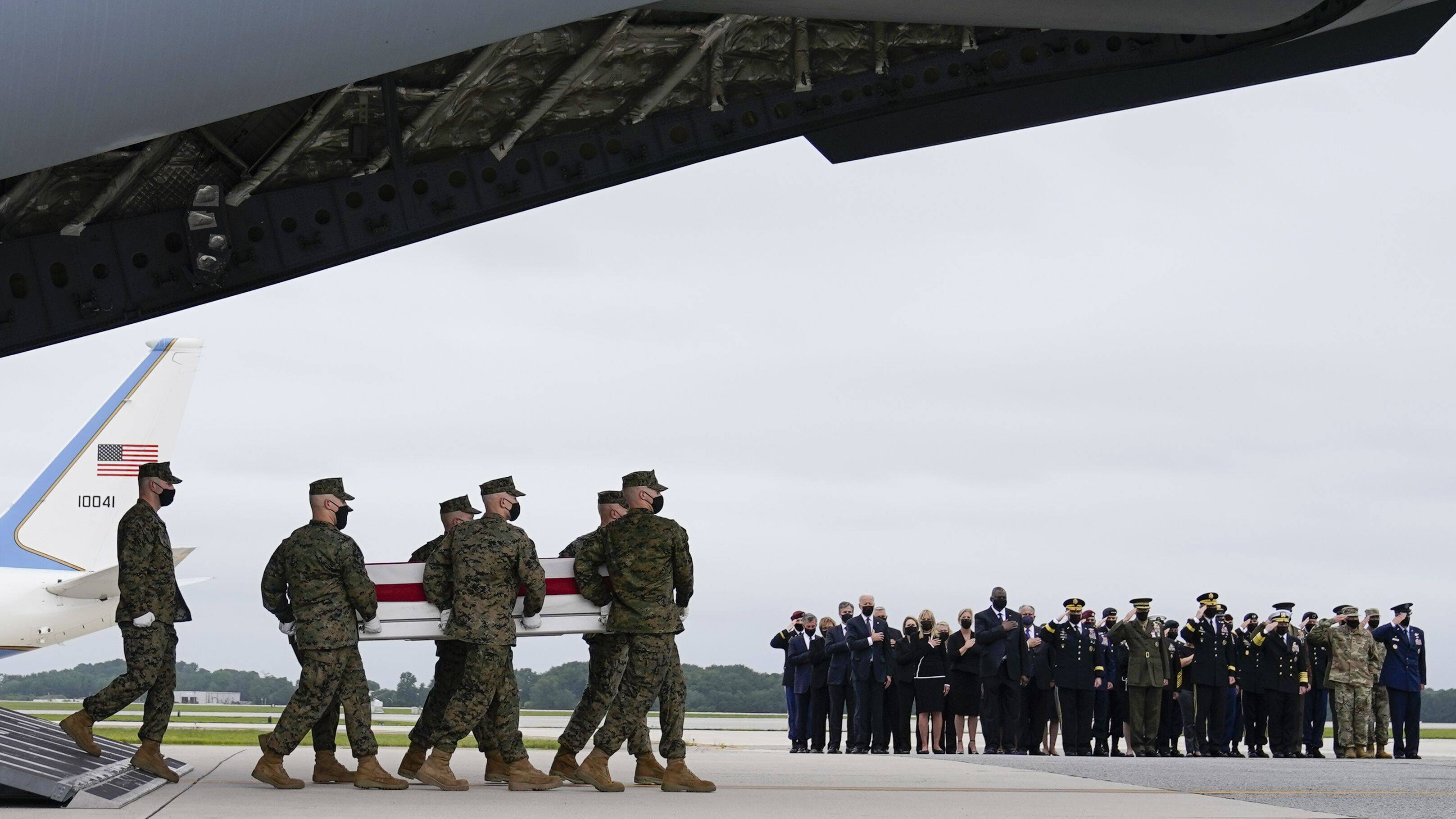 President Biden, first lady Jill Biden and others watch as a Marine Corps team carries the remains of Marine Corps Lance Cpl. Jared M. Schmitz, 20, during a casualty return on Aug. 29 at Dover Air Force Base in Delaware. (Carolyn Kaster/AP)