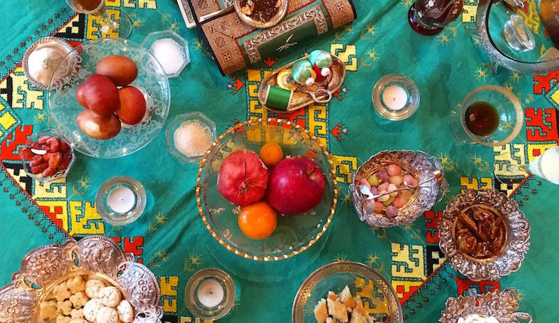 The haftseen table, one of the main customs of Nowruz, includes seven items to symbolize wishes for the year to come. Niloo Farhad's haftseen includes several extra items, like burnt cookies, candies, and a mirror for splashing rosewater when arriving hom