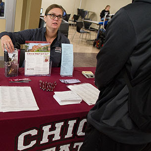 Chico State admission representative sitting at a table talking to a student