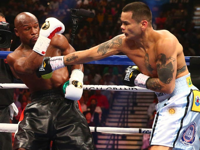 Marcos Maidana punches as Floyd Mayweather Jr. defends during their fight at MGM Grand.