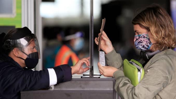 Uma passageira usando uma máscara facial mostra seu passaporte e cartão de embarque para um funcionário em um posto de controle de segurança no Aeroporto Internacional El Dorado, em Bogotá, em 1º de setembro de 2020.
