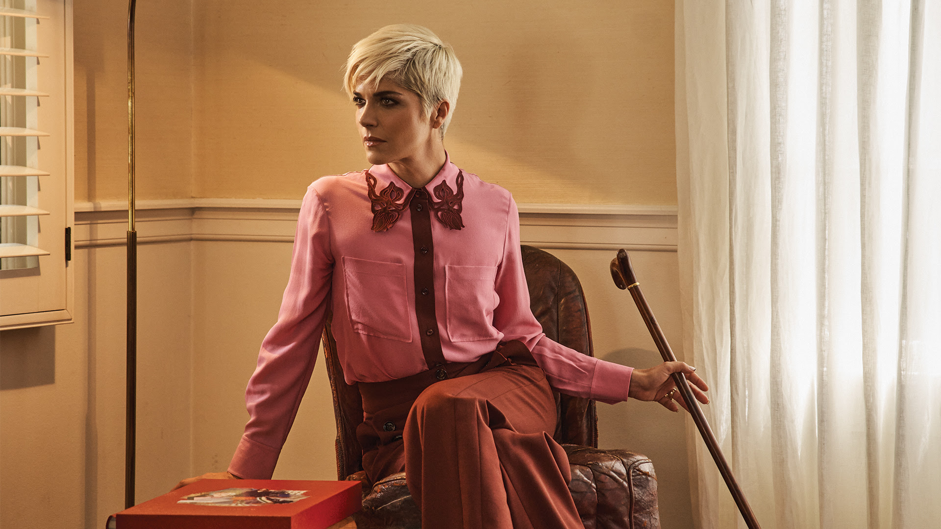 Selma Blair, a woman with short blonde hair sits on a chair with her walking cane in one hand. She is dressed in purple and red